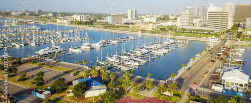 Panorama aerial view waterfront harbor Corpus Christi with marina and downtown skylines in background. Yacht, sailboat is moored at the quay. Top pier speedboat in marina lot filled full row of boat