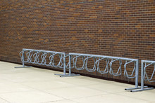 Sturdy Metal Bicycle Rack In Front Of A Traditional Brown Brick Wall Background In Varying Shades Of Brown, Blue And Red