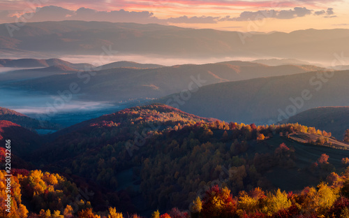 In de dag Grijs gorgeous red sunrise in mountains. forested hills in colorful fall foliage. fog in the distant valley