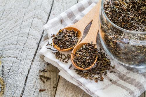 Dry black tea in wood spoon