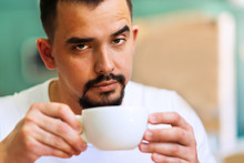 Handsome Man With Raised Eyebrow And Ironical Face Looking At Camera Over The White Hot Mug Of Morning Coffee. Morning Coffee Ritual. Room For Text