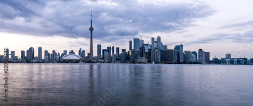 Long exposure of wide panorama of Toronto, Ontario - Canada. Bright sky with a smooth water surface. Beautiful city lights seen from the Toronto Island.