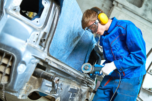 collision repairs service. mechanic grinding car body by grinder Canvas Print