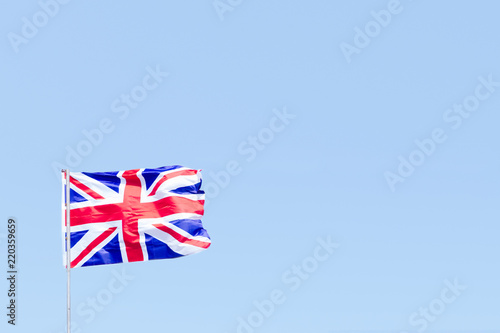 Union Jack flag of Great Britain UK Blowing in the wind against a empty blue sky Wallpaper Mural