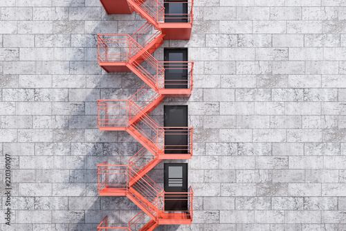 Canvas Print Gray bricks building, red fire escape stairs