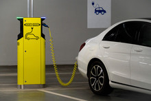 Electric Car Is Charged At The Charging Station In The Underground Parking Lot