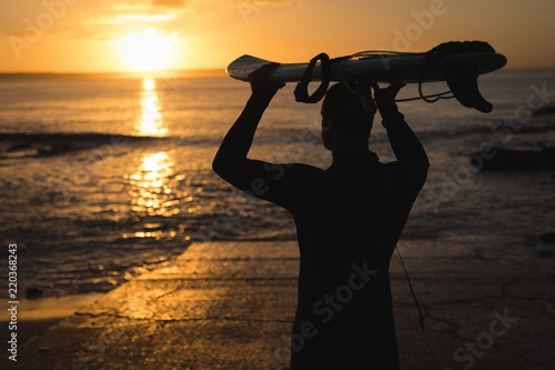Surfer carrying the surfboard on his head