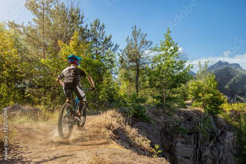 Foto op Aluminium Fietsen Mountain biker on forest trail. Male cyclist rides the rock