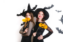 Two Happy Women In Black Witch Halloween Costumes With Pumpkin On Party Over White Background