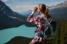 Female Hiker Looking Through Binoculars At Countryside
