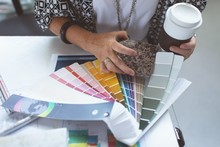 Female Executive Checking Color Swatch On Drafting Table In