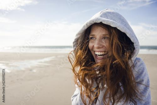 Woman having fun on a windy beach, wearing hood
