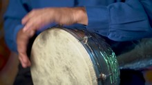 Closeup Of Hands Playing Slow Drumming Rhythm On Metal Turkish Daholla With Arabic Background.