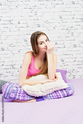 4e9159876ff6d4 Cute young woman at home, sitting in bed, wearing pajamas, smiling and being  shy. Studio lighting, no retouch, brick wall background.
