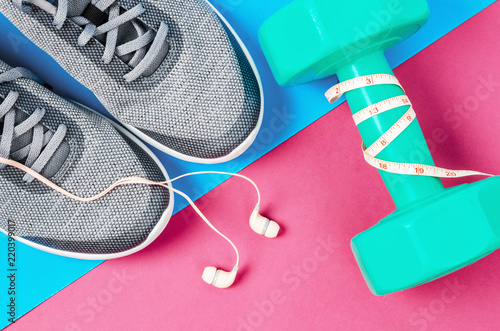 Photo  Green dumbbell and sneakers.