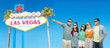 entertainment, leisure and friendship concept - group of happy smiling friends in sunglasses pointing finger to something over welcome to fabulous las vegas sign background