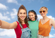 friendship and people concept - group of happy female smiling friends in sunglasses taking selfie over blue sky and clouds background