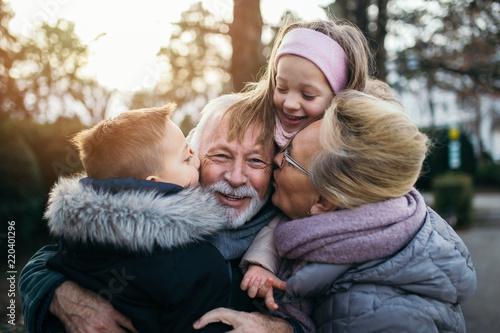 Obraz Grandparents having fun with their grandchildren in city park. - fototapety do salonu