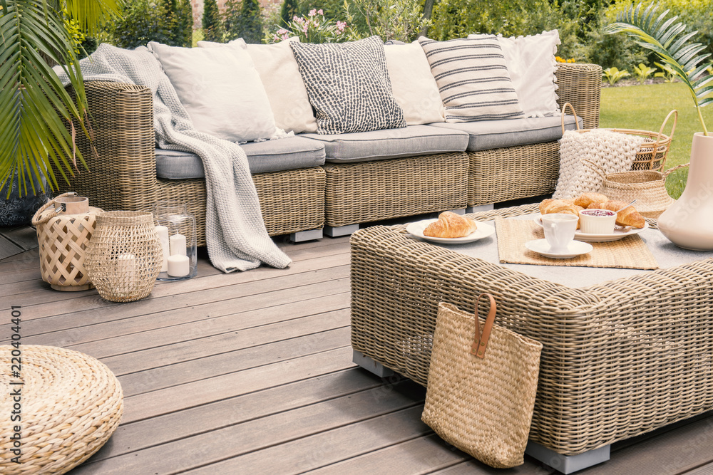 Fototapety, obrazy: Wicker patio set with beige cushions standing on a wooden board deck. Breakfast on a table on a backyard porch.