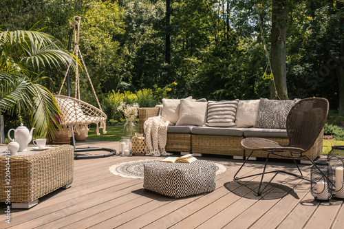 A rattan patio set including a sofa, a table and a chair on a wooden deck in the sunny garden Wallpaper Mural