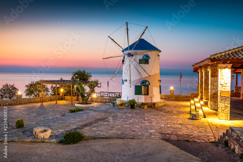Fabulous morning scene on the Potamitis Windmill. Colorful spring sunrise on the Zakynthos island, Ionian Sea, Greece, Europe. Beauty of countryside concept background.