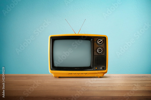 Fotografie, Tablou Yellow Orange color old vintage retro Television on wood table with mint blue background