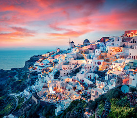 Fototapeta Słynne budowle i znane miejsca Impressive evening view of Santorini island. Picturesque spring sunset on the famous Greek resort Oia, Greece, Europe. Traveling concept background. Artistic style post processed photo.