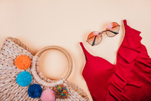 Summer Fashion Flatlay With Gradient Round Sunglasses, Trendy Straw Bag With Pompoms And Red Swimsuit With Frills On The Beige Background. Perfect Beach Set For Holidays On The Sea. Marina Style.