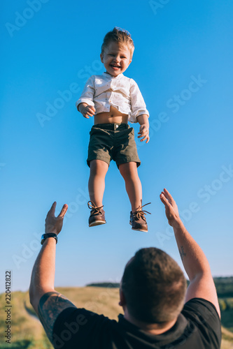 father throwing up adorable happy little son against blue sky Wall mural