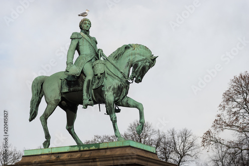 Fotografia  Oslo royal palace monument of king karl johan with bird on head, view from parkw