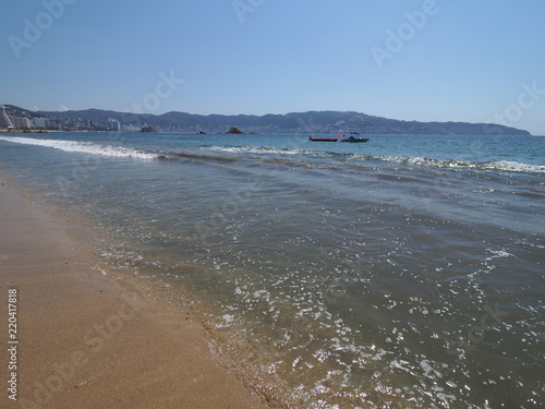 Fotografija  Great landscape of sandy beach at bay of ACAPULCO city in Mexico with motor boat
