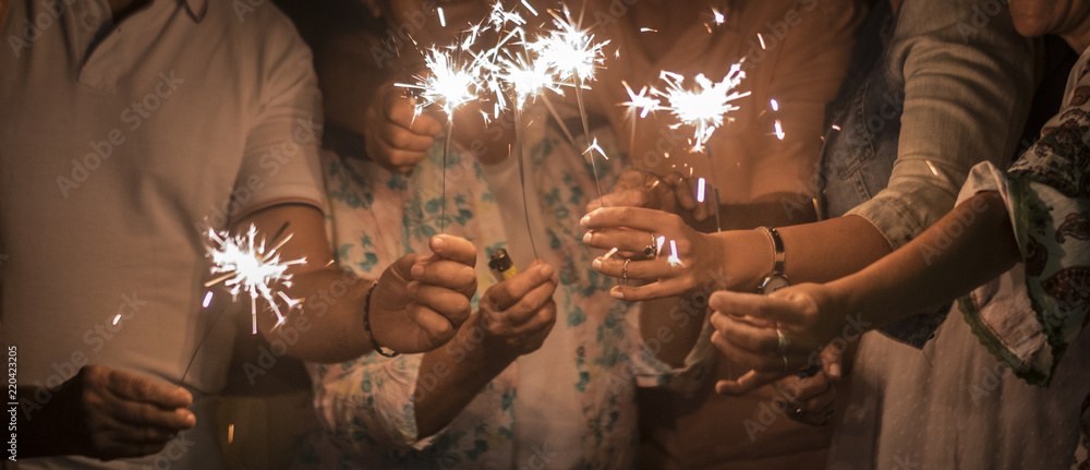 Fototapeta panoramic view of group of friends mixed ages celebrate together in the night with sparkles file light. new year eve or birthday or christmas event to live friednship and familuy with happiness