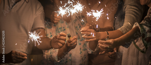 Obraz panoramic view of group of friends mixed ages celebrate together in the night with sparkles file light. new year eve or birthday or christmas event to live friednship and familuy with happiness  - fototapety do salonu