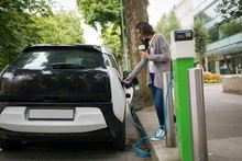 Woman Charging Electric Car At...