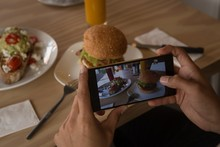 Woman Taking Photo Of Food In Cafe
