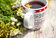 Herbal Tea In A Cup And A Bouquet Of Medicinal Flowers On An Old Wooden Surface, Toned Phytotea From Autumn Herbs. Traditional Medicine.