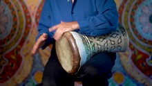 Wide Shot Of Playing Rhythm On Clay Doumbek With Fish Skin Head.