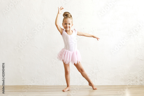 Little blonde balerina girl dancing and posing in dance club with wooden floot an white textured plaster wall Fototapet