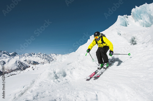 Fotografie, Obraz  Professional skier at the speed before jumping from the glacier in winter agains