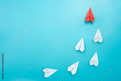 Photo Leadership concept with red paper plane leading among white on blue background