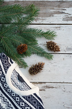 Top View On White And Black Gray Knitted Sweater On Winter Christmas Patternt On Wooden Background With Branches Of Fir Tree. Wool.