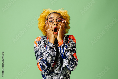 Fotografija  Young woman with mouth wide open, isolated on green studio background