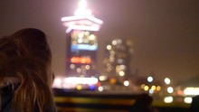 A Shot Of A Girl Standing Before The Amsterdam Tower And The Eye Film Museum On The Ferry By Night