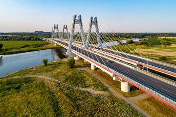 New modern double cable-stayed bridge over Vistula River in Krakow, Poland. Part of the ring motorway around Krakow under construction. Aerial view at sunset. Sedzimir Steel mill in the background.