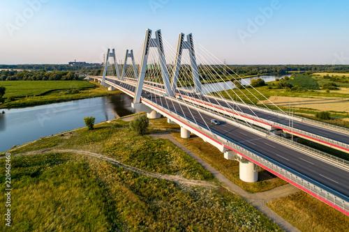 Foto auf Gartenposter Bridges New modern double cable-stayed bridge over Vistula River in Krakow, Poland. Part of the ring motorway around Krakow under construction. Aerial view at sunset. Sedzimir Steel mill in the background.
