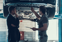 Auto Mechanic Showing Client Car Problem