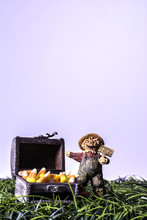 Scarecrow Figurine Standing In Green Grass Holding A Happy Fall Sign Next To Wood Chest Full Of Candy Corn On Vertical White Background With Room For Copy