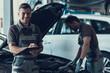 Two Handsome Mecanics Repairing Car in Garage