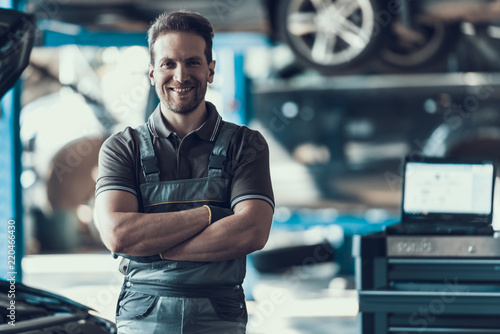 fototapeta na lodówkę Handsome Smiling Car Machanic Standing in Garage