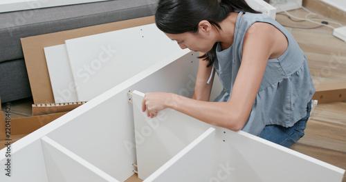 Photo  Woman assembling a shelf at home